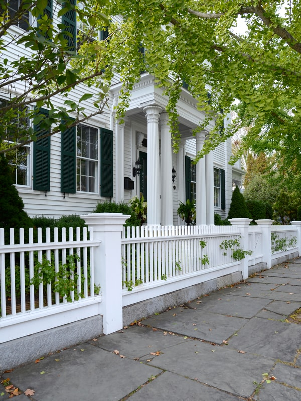 White Picket Fence With White Colonial House And Lush Green Trees.