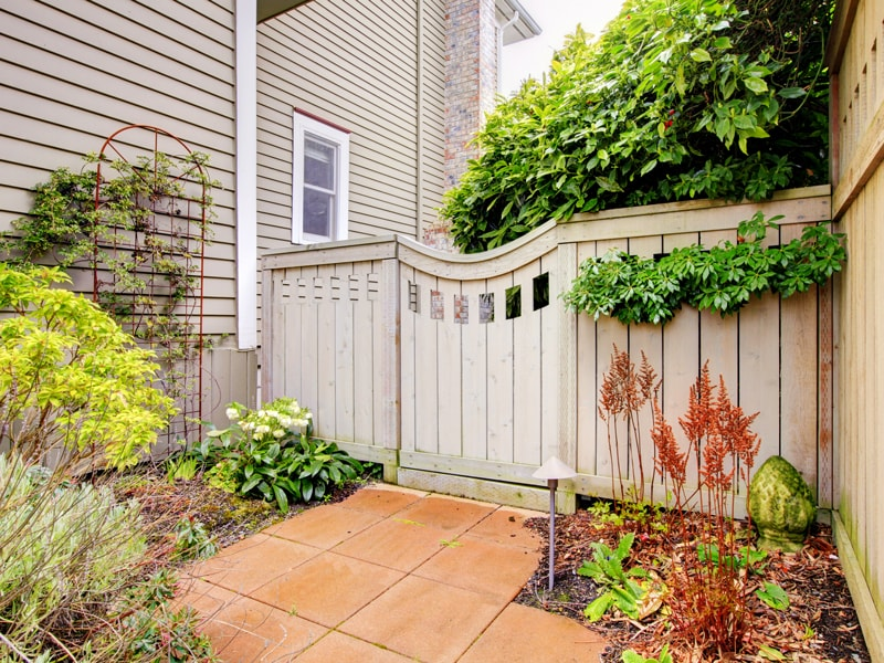 Decorative Custom Wood Gate And Fence With Lush Greenery.