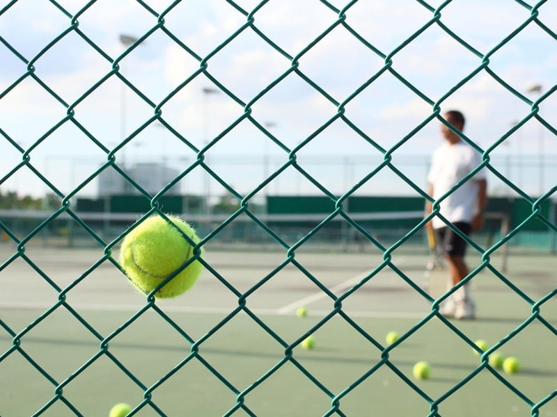 Green Coated Chain Link Fence With A Tennis Ball Stock In It With A Tennis Player In The Back
