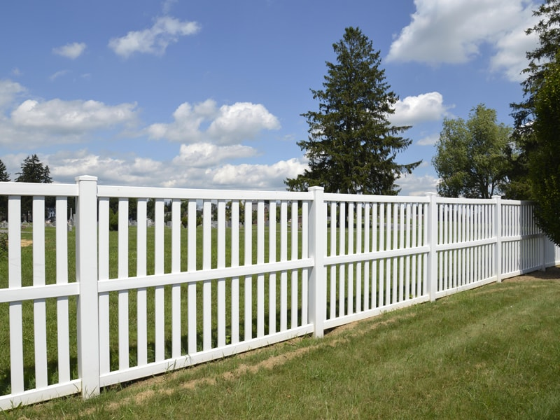 White Vinyl Fence Separating Two Large Fields Of Green Grass
