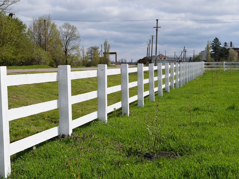 White Wood Farm Fencing Separating Two Large Fields Of Green Grass