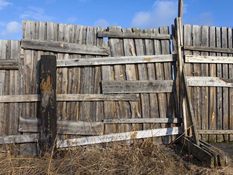Old Weathered And Rotted Fence That Is Leaning Every Which Way In Need Of Repair