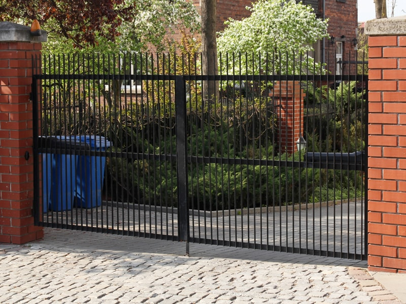 Black Metal Driveway Gate With Brick Posts.