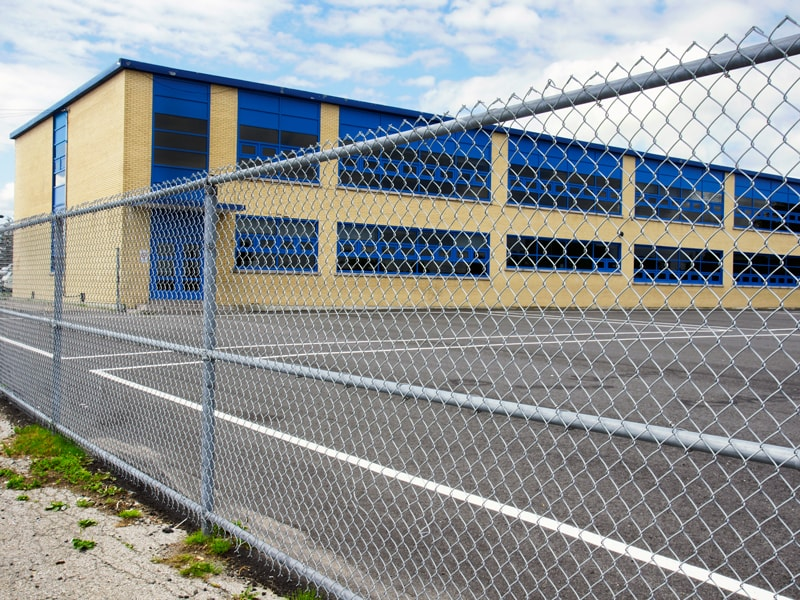 Chain Link Fence Outside A Blue And Yellow School Or Municipal Building