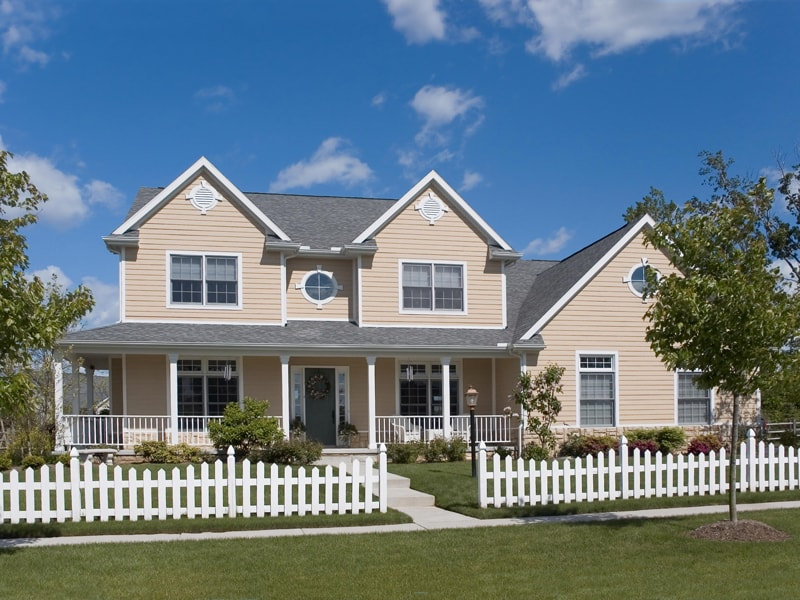 White Picket Fence And Tan Two Story House With Grey Roof