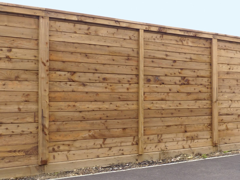 Fifteen Foot Hight Pine Divider Fence For A Sound Barrier